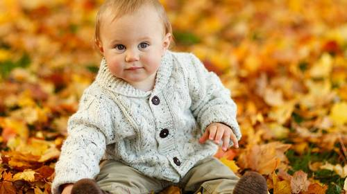baby surrounded by autumn leaves