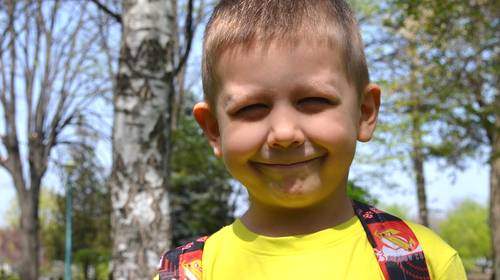 little boy with yellow shirt and backpack smiling