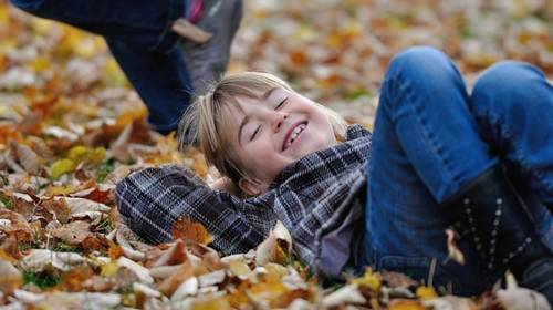 boy smiling laying on leaves