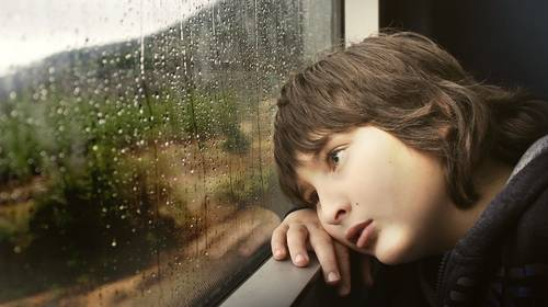 boy looking out rainy window