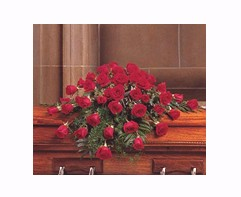 casket covered in red roses