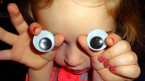 small child holding eye buttons