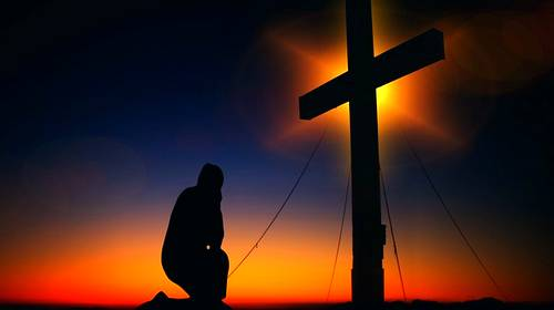 kneeling at a cross at sunrise sunset