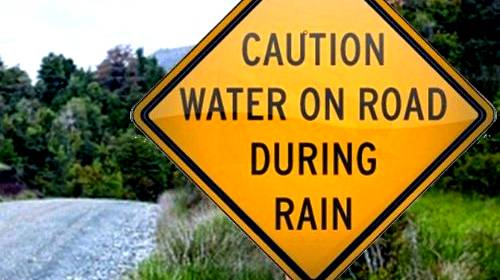 caution sign water on road during rain