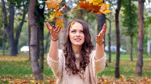 girl throwing leaves into the air