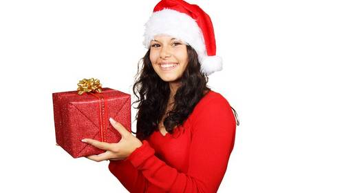girl in santa hat with present