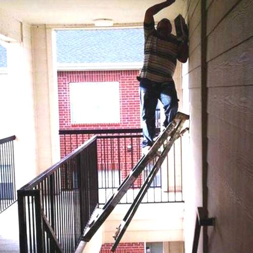 man on dangerous ladder on staircase