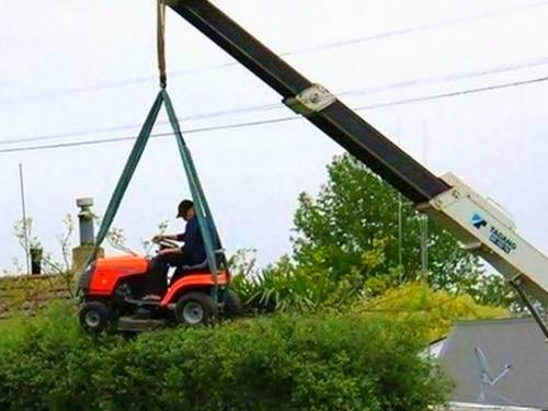 man mowing roof from crane