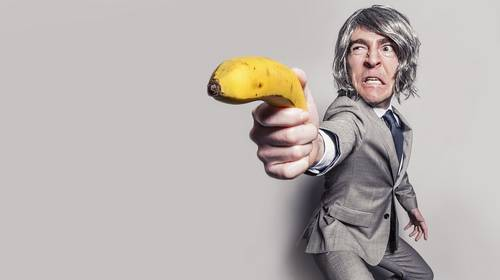 businessman aiming a banana