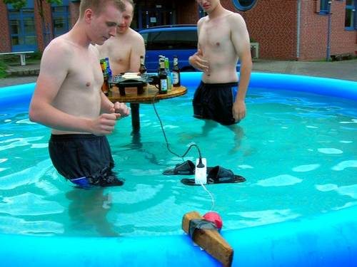 men in pool with electric cords