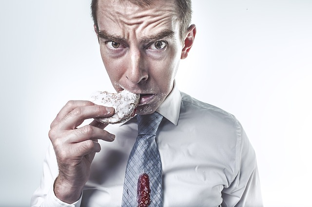 man eating donut jelly on tie