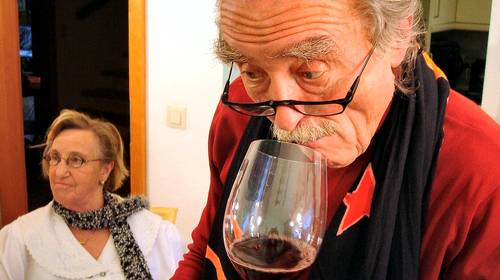 elderly man sniffing red wine glass