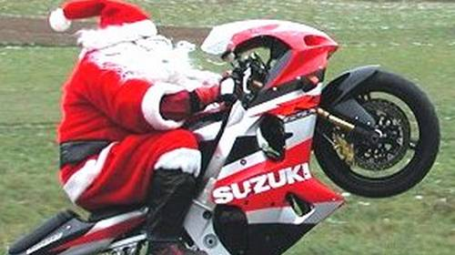 Santa Claus riding a motorcycle popping a wheelie