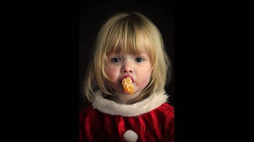 little santa girl eating an orange